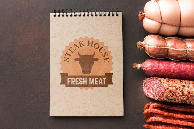 Produtos à base de carne com maquete de bloco de notas