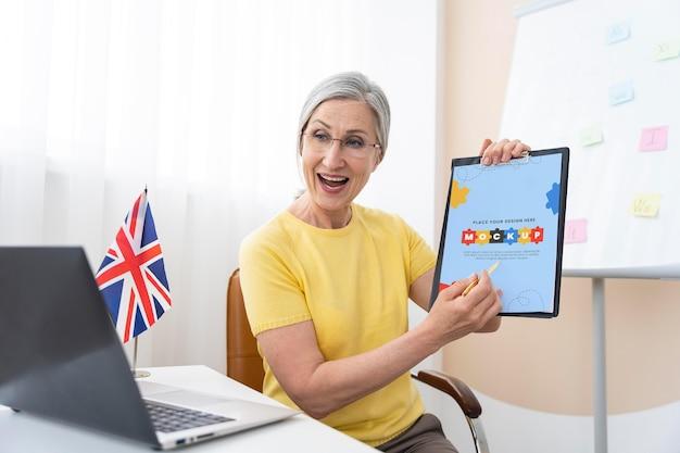 Professora de inglês segurando uma maquete de tablet