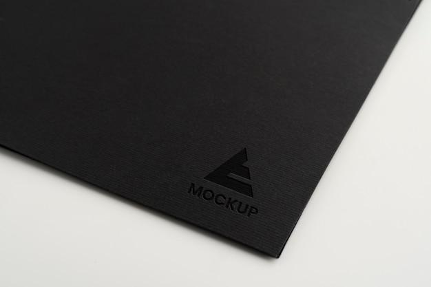Projeto do logotipo da maquete em letras maiúsculas em papel preto minimalista Psd Premium