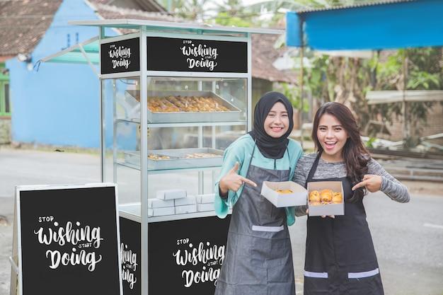 Proprietário da empresa, mostrando seu produto de bolo fresco na maquete de barraca de comida