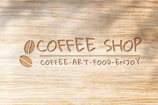 Psd de maquete de logotipo deboss para café em fundo de textura de madeira