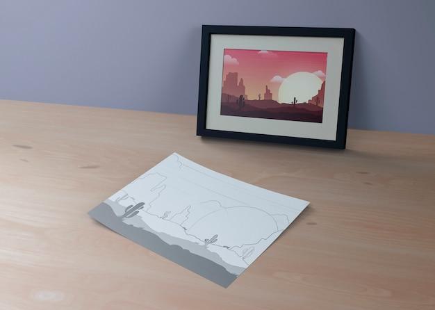 Quadro com paisagem e desenho na folha ao lado