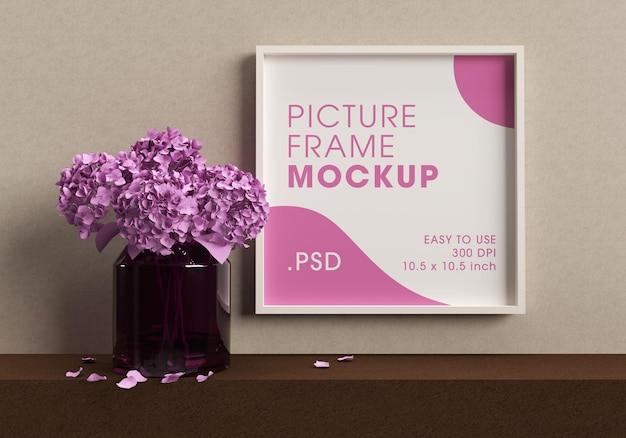 Quadro de pôster ao lado de um vaso com renderização de design de maquete de flores