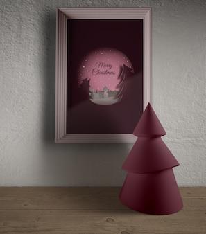 Quadro enganchado na parede com miniatura tre de natal
