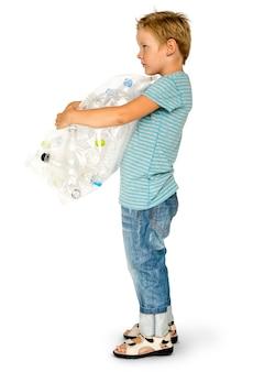 Rapaz pequeno da ecologia que guarda o saco da garrafa plástica para reciclar