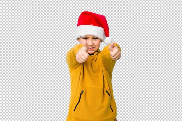Rapaz pequeno que comemora o dia de natal que veste um chapéu de santa com polegares levanta, felicidades sobre algo, apoia e respeita o conceito.