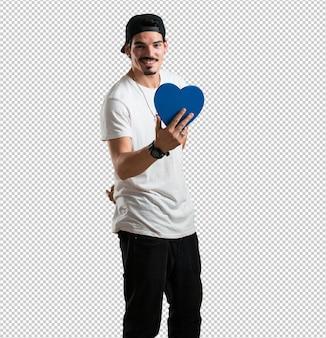 Rapper jovem alegre e confiante, oferecendo uma forma de coração para a frente