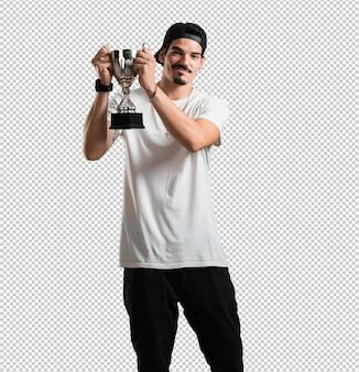 Rapper jovem animado e enérgico, levantando um copo depois de ter alcançado uma vitória difícil, recompensa pelo trabalho duro, confiante e positivo