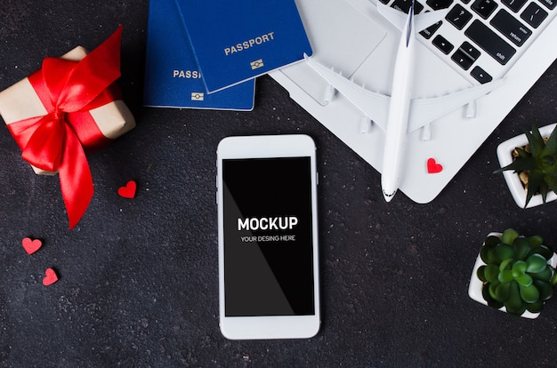 Reserva de viagem com smartphone, modelo de avião, laptop, passaporte e caixa de presente