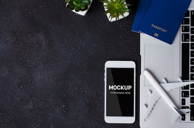 Reserva de viagens com modelo de laptop, passaporte, smartphone e avião