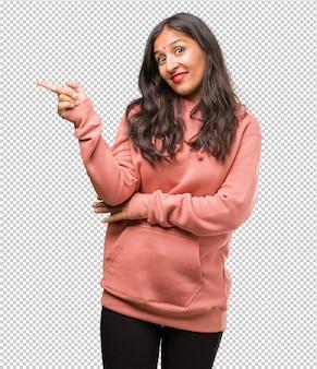 Retrato, de, condicão física, jovem, indianas, mulher aponta, ao lado, sorrindo, surpreendido, apresentando