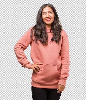 Retrato, de, condicão física, jovem, indianas, mulher, com, mãos quadrils, ficar, relaxado, e, sorrindo