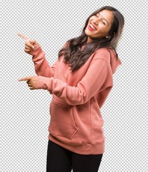 Retrato de fitness jovem indiana apontando para o lado, sorrindo surpreso apresentando algo, natural e casual