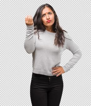 Retrato de jovem indiano, fazendo um gesto típico italiano, sorrindo e olhando para a frente