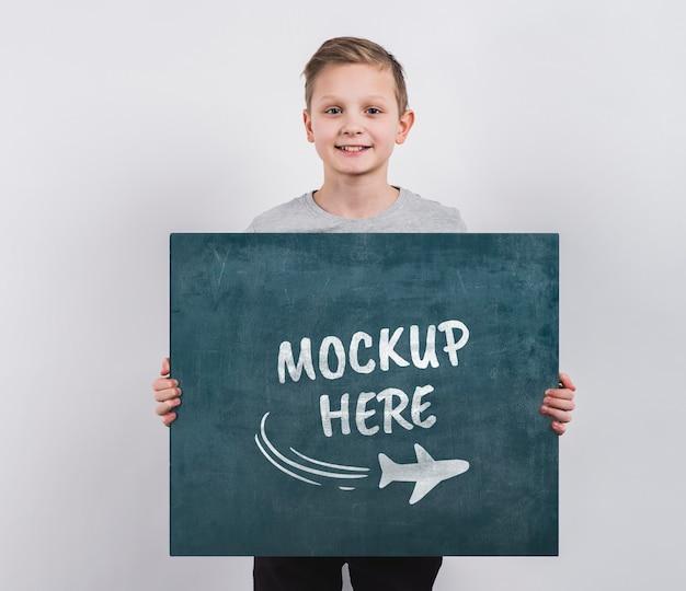Retrato de menino segurando uma placa de maquete