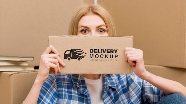 Retrato de mulher segurando uma placa de entrega com maquete