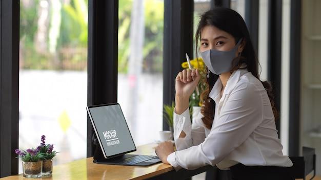 Retrato de mulher usando máscara enquanto trabalha com tablet digital em um café