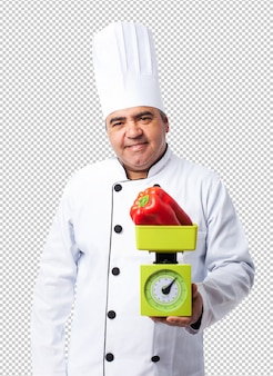 Retrato de um homem cozinheiro pesando uma pimenta vermelha