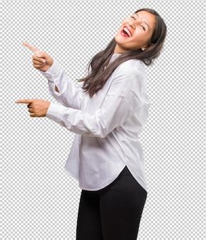Retrato de uma jovem indiana apontando para o lado, sorrindo surpreso apresentando algo natural e casual