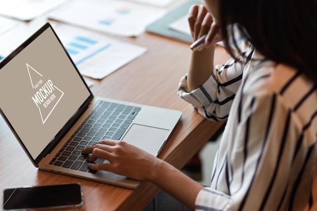 Retrato recortado de mulher de negócios navegando em um laptop genérico com a tela da área de trabalho em branco no escritório