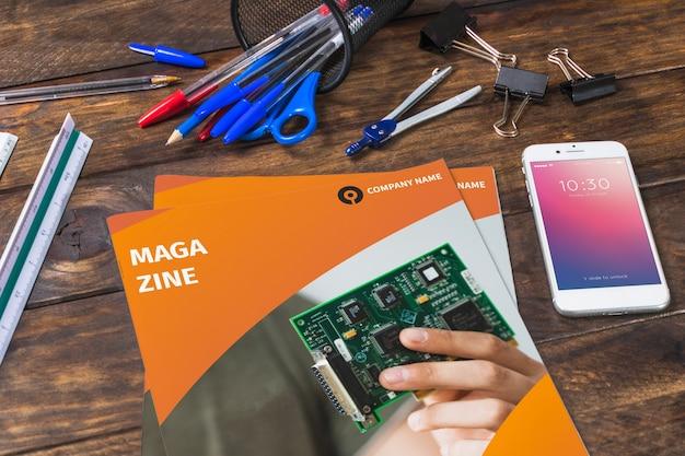 Revista e smartphone maquete na mesa de madeira com canetas e governantes Psd grátis