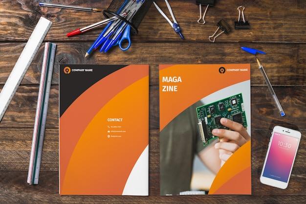 Revista e smartphone maquete na mesa de madeira com canetas e governantes