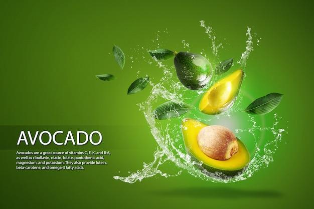 Salpicos de água no abacate verde fatiado fresco sobre o bac verde