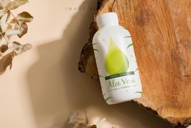 Simule a garrafa em um corte de madeira e superfície bege Psd Premium