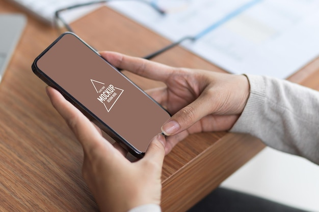 Simule a tela do celular em branco segurando com as duas mãos na mesa de madeira com material de escritório