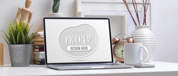 Simule o laptop na mesa de trabalho com livros, suprimentos e decorações na sala de escritório