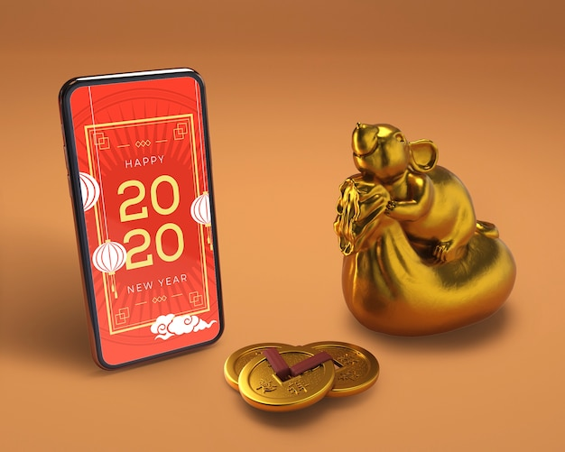 Smartphone ao lado da estátua de ouro para o ano novo