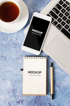 Smartphone branco com tela em branco preta na mesa de escritório com laptop, caderno vazio e xícara de chá