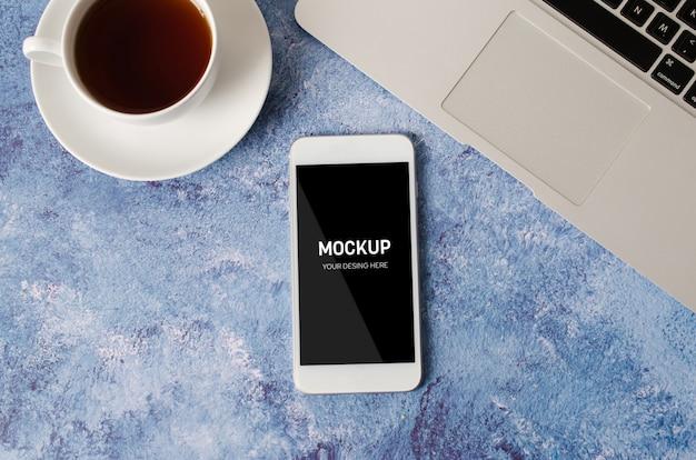Smartphone branco com tela em branco preta na mesa de escritório com laptop e xícara de chá