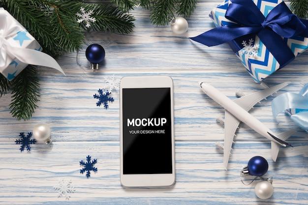 Smartphone com tela de maquete com modelo de avião entre as decorações de natal