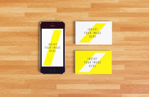 Smartphone e cartão de visita em fundo de madeira maquete