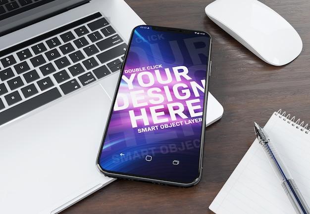 Smartphone moderno deitado em uma maquete de laptop