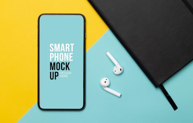 Smartphone preto com tela e fones de ouvido sem fio e notebook