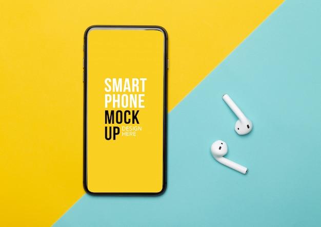 Smartphone preto com tela e fones de ouvido sem fio em amarelo e azul.