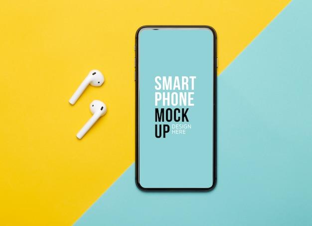 Smartphone preto com tela e fones de ouvido sem fio em fundo amarelo e azul.