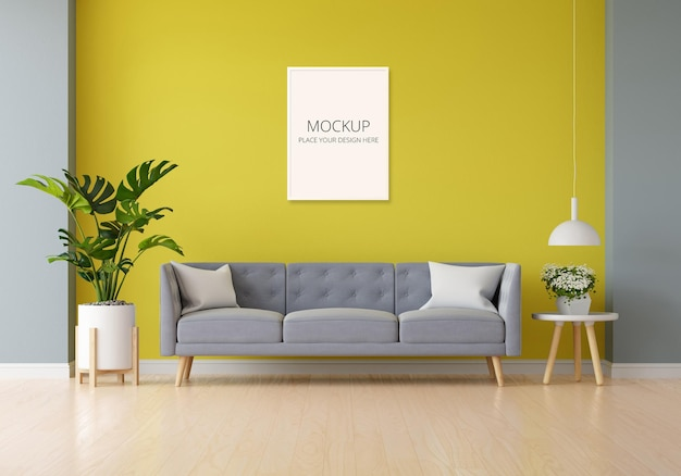 Sofá cinza na sala de estar amarela com maquete de moldura