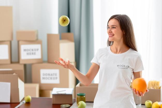 Sorridente voluntária jogando maçã para o alto
