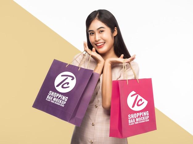 Sorrindo linda mulher asiática segurando modelo de maquete de sacolas de compras para seu projeto