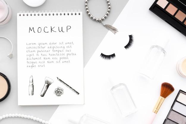 Sortido de cosméticos de maquiagem com mock-up de bloco de notas
