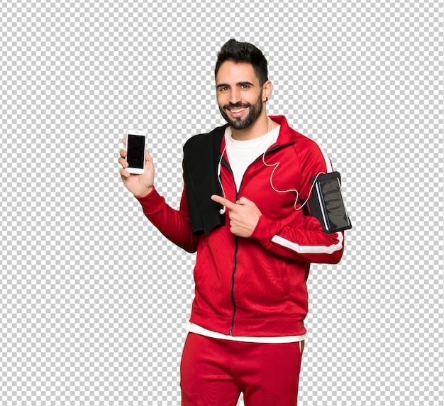 Sportman bonito feliz e apontando o celular