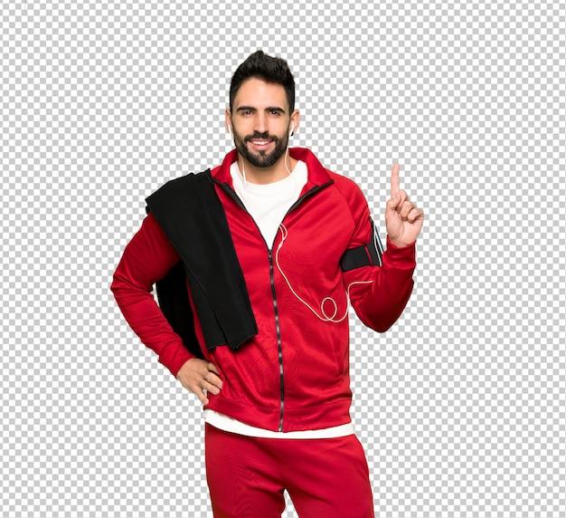 Sportman bonito mostrando e levantando um dedo no sinal dos melhores