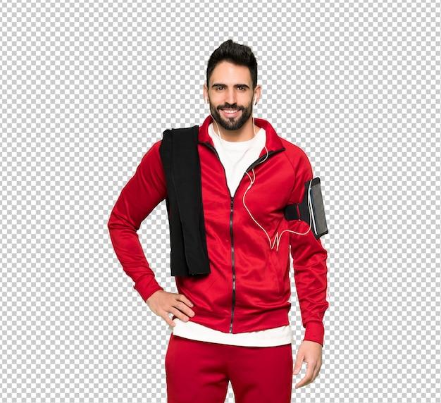 Sportman bonito posando com os braços no quadril e sorrindo