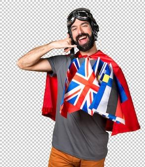 Super-herói com um monte de bandeiras fazendo gesto de telefone