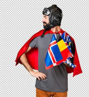 Super-herói com um monte de bandeiras olhando lateral