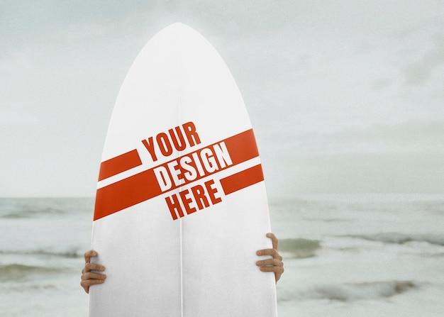 Surfista segurando uma maquete de prancha de surf