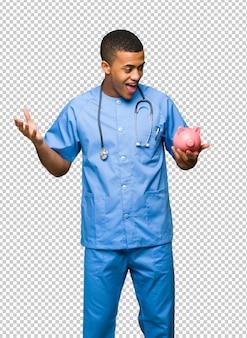Surgeon médico homem surpreendido enquanto segura um piggybank